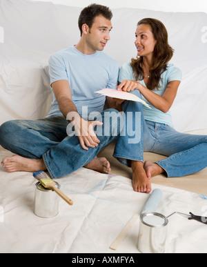 Couple assis sur toile à la peinture sur panneau Nuancier Banque D'Images