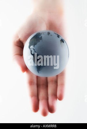 Main tenant un globe miniature