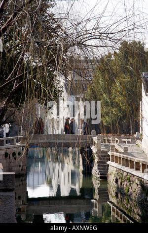 Les gens qui marchent sur un pont de pierre à travers le canal historique à Suzhou Chine Banque D'Images