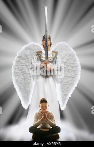 Fille priant avec angel la protéger Banque D'Images