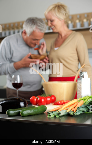 Une femme blonde vous permet de goûter à l'homme aux cheveux gris quelque chose qu'elle a cuit, selective focus Banque D'Images
