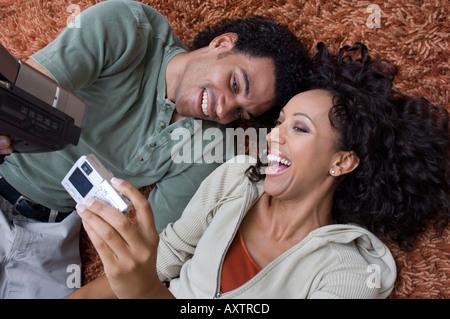 Portrait d'un couple d'enregistrement vidéo tout en posant sur le tapis. Banque D'Images