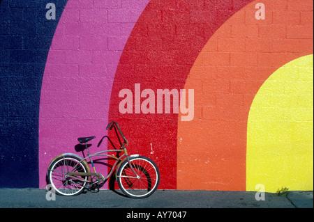 Vieux vélo appuyé contre un mur de couleur arc-en-ciel