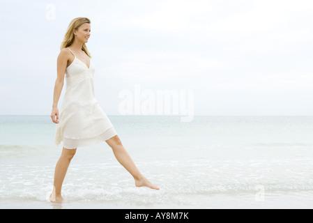 Jeune femme en robe d'été prenant grand pas comme elle marche dans l'eau peu profonde sur la plage, pleine longueur Banque D'Images