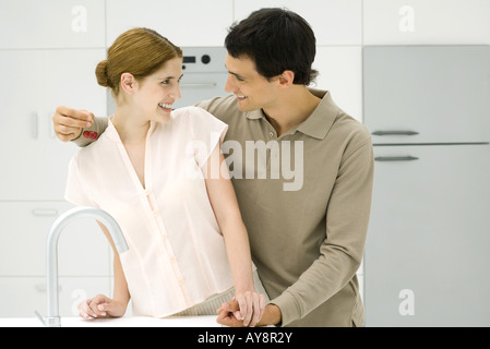 Couple holding hands in kitchen, smiling, cerises Banque D'Images