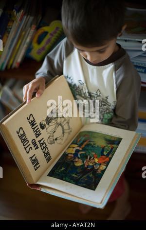 Garçon âgé de 6 ans lit livre de contes et comptines Banque D'Images