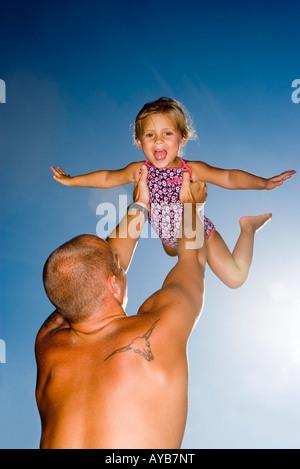 Jeune fille père tient en l'air Banque D'Images