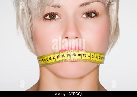 Femme avec ruban de mesure sur sa bouche Banque D'Images