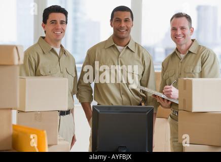 Livreur multi-ethnique à côté d'ordinateur Banque D'Images