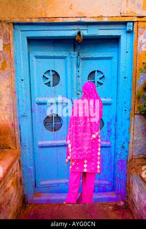 Femme dans la vieille ville de Delhi par une porte colorée, Inde Banque D'Images