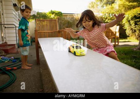 Frère et soeur jouer avec de petites voitures sur une rampe en pente fille âgée de quatre ans, garçon de 6 ans