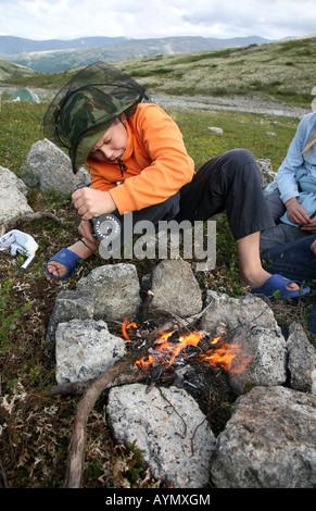 Jeune garçon d'allumer un feu au cours d'un trekking dans la montagnes Khibiny de la péninsule de Kola, Russie Banque D'Images