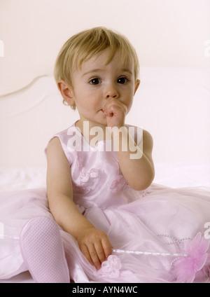 Assez petite fille en rose robe de soirée sucking thumb Banque D'Images