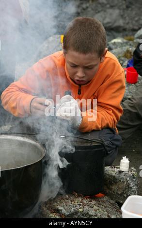 Jeune garçon cuisson sur le feu pendant un trekking dans les montagnes Khibiny de la péninsule de Kola, Russie Banque D'Images