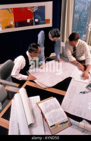 Vue de dessus de la cuisine asiatique et caucasienne dans leur réunion du bureau d'ingénieurs et d'examiner les Banque D'Images