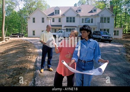 Nouveaux propriétaires d'inspecter la propriété de leur maison nouvellement construite avec l'agent immobilier et Banque D'Images