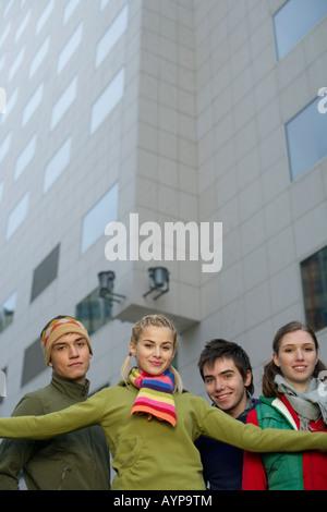 Groupe de jeunes gens debout en face d'un immeuble de grande hauteur Banque D'Images