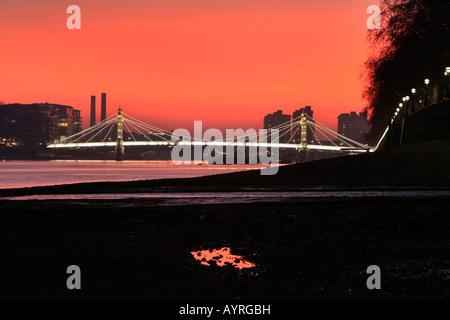 Albert Bridge peu après le coucher du soleil, le feu-rouge ciel vu à partir de la banque de la Thames, Chelsea Embankment, Banque D'Images