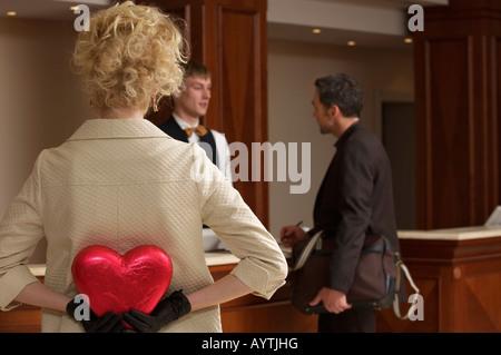L'homme à la réception de l'hôtel, femme cache un coeur de chocolat Banque D'Images