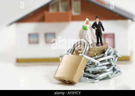Suite Nuptiale figurines couple sur une pile de pièces enveloppé d'une chaîne avec cadenas, maison miniature en Banque D'Images