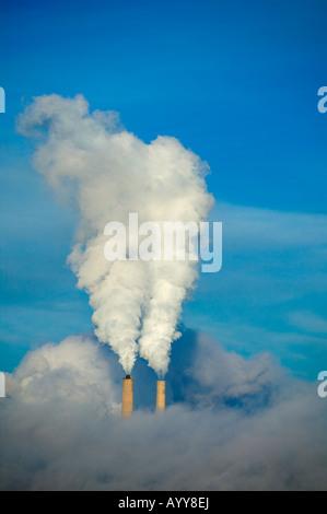 Encadrée par un brillant ciel bleu, une centrale électrique produisant de l'électricité les panaches de vapeur ou Banque D'Images