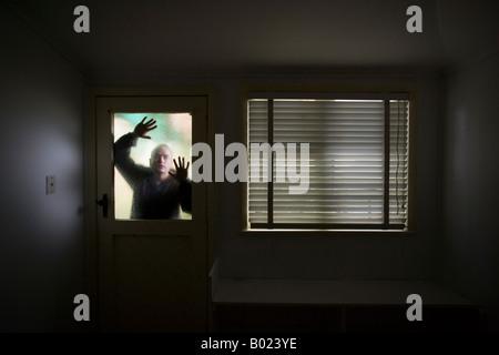 L'homme ressemble en salle à travers le verre dépoli de la fenêtre sur la porte à côté fenêtre avec blind Banque D'Images