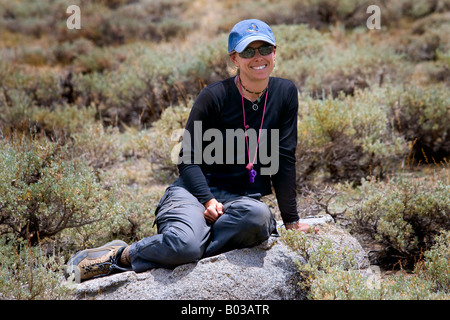 Active woman sitting on rock dans les montagnes Banque D'Images