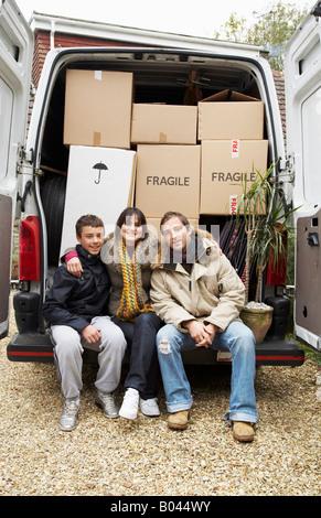 Famille assis sur l'arrière du camion de déménagement Banque D'Images