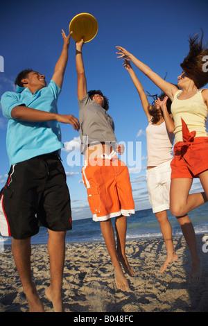 Amis jouant sur Frisbee Beach Banque D'Images