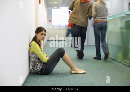 Jeune femme assise sur le sol d'un couloir Banque D'Images