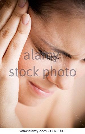 Femme avec des maux de tête, tenant sa main à sa tempe Banque D'Images