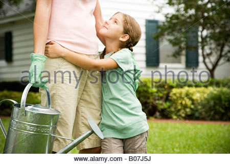 Daughter hugging mère portant arrosoir Banque D'Images