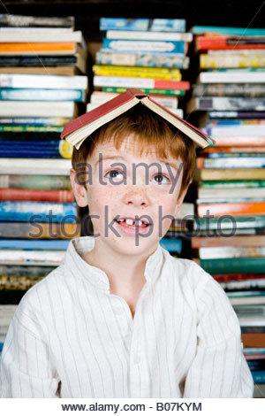 Garçon brun de gingembre avec livre sur sa tête Banque D'Images