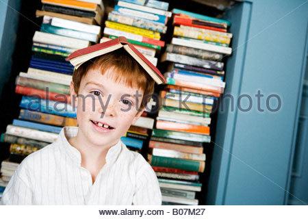 Le gingembre jeune garçon brun avec livre sur sa tête Banque D'Images