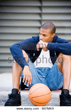 Portrait of a young African American man sitting with a basket-ball. Banque D'Images