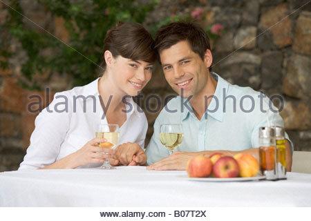 Un couple partageant une bouteille de vin à une table Banque D'Images