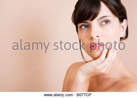 Portrait d'une jeune femme aux cheveux noirs en chignon, le menton dans sa main, pensant Banque D'Images