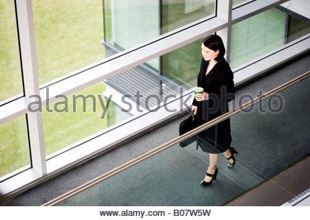Businesswoman dans immeuble de bureaux modernes, d'arriver pour le travail Banque D'Images