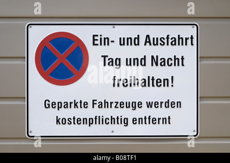 """No parking sign, Ein- und Ausfahrt Tag und Nacht freihalten! Geparkte Fahrzeuge werden nicht möglich abgeschleppt"""" Banque D'Images"""