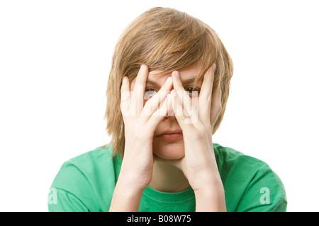 13-year-old hoy couvrant son visage avec ses mains Banque D'Images