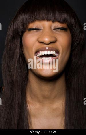 Portrait d'une jeune femme à la peau sombre rire Banque D'Images