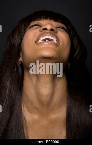 Portrait d'une jeune femme à la peau sombre de rire, la tête en arrière Banque D'Images