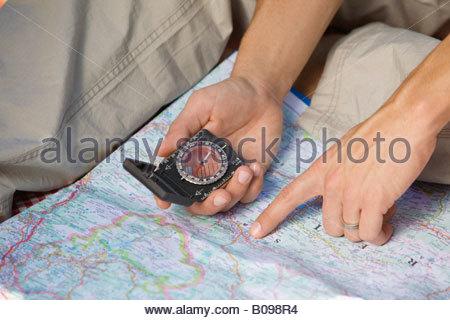 Détail de man holding Compass pointant sur la carte Banque D'Images