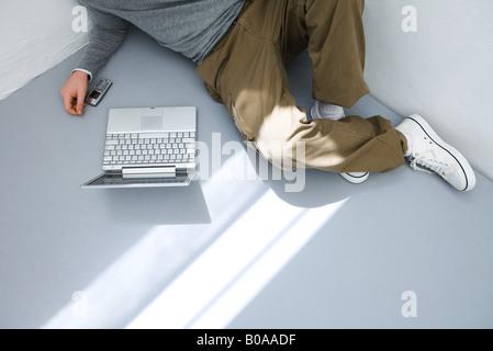 Jeune homme assis sur le sol en face d'ordinateur portable, cropped view Banque D'Images