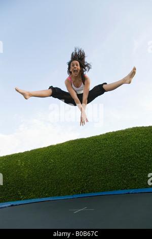Jeune femme trampoline; une adolescente à l'âge de 16 ans sur un trampoline jumping, UK Banque D'Images