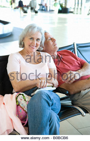 Senior couple sitting in airport departure lounge, l'homme se penchant sur l'épaule de la femme, dormir, woman smiling, Banque D'Images
