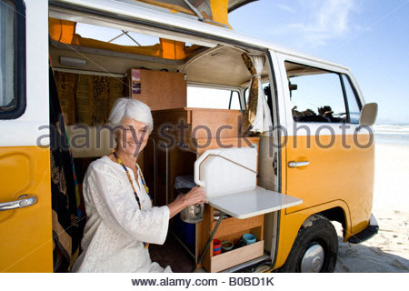 Senior woman faire du thé dans le camping-car sur la plage, smiling, portrait, close-up Banque D'Images