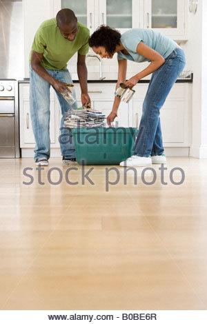 Jeune couple mise en pots de verre, de canettes et de journaux en bac de recyclage dans la cuisine, low angle view Banque D'Images