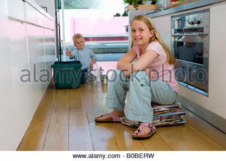 Fille sur l'ensemble de journaux dans la cuisine, frère 2-4 mettre dans le bac de recyclage en arrière-plan, smiling, Banque D'Images