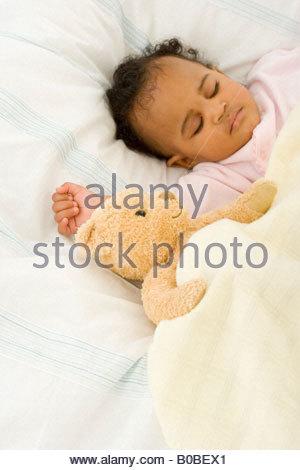Bébé fille 3-6 mois endormi dans le lit avec soft toy Banque D'Images